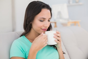 Woman drinking coffee on couch