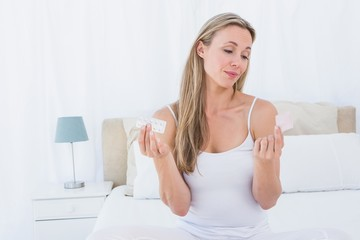 Woman choosing her medicine on bed