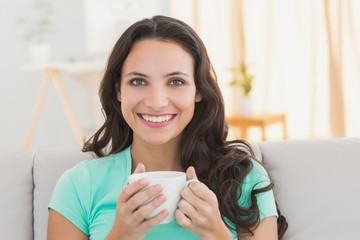Pretty brunette relaxing on the couch with coffee