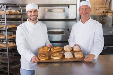 Team of bakers smiling at camera with trays of bread