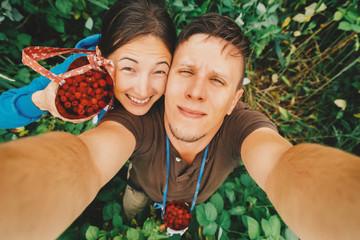 Couple in love taking self-portrait in summer raspberry garden
