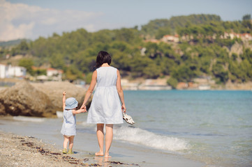 Mother and Girl Walking on Beach