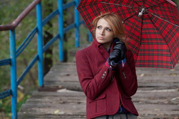Attractive blonde woman posing under a red umbrella