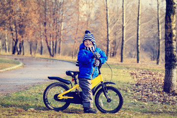happy little boy with bike in autumn park
