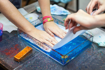 Two people print inks of marbling into silk from water surface