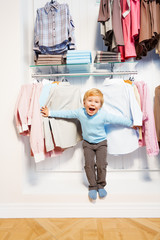 Laughing boy standing among clothes in the shop