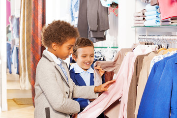 Two boys choose clothes in store while shopping