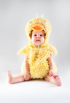 Image of a little funny baby in a duck costume
