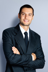 Happy businessman with crossed arms, on grey
