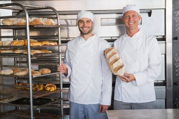 Smiling colleagues holding fresh loaves