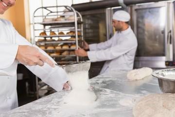 Smiling baker sieving flour on the dough