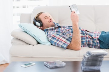 Relaxed man listening music lying on sofa