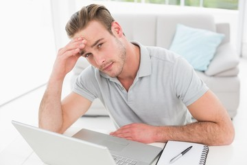 Anxious businessman using laptop and notebook