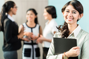 Indonesian Business woman in front of team