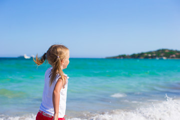 Adorable little girl having fun during tropical beach vacation