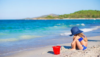 Adorable little girl in big blue straw hat at white beach