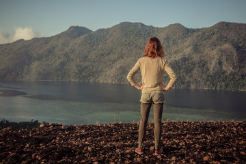 Woman standing on mountain overlooking bay