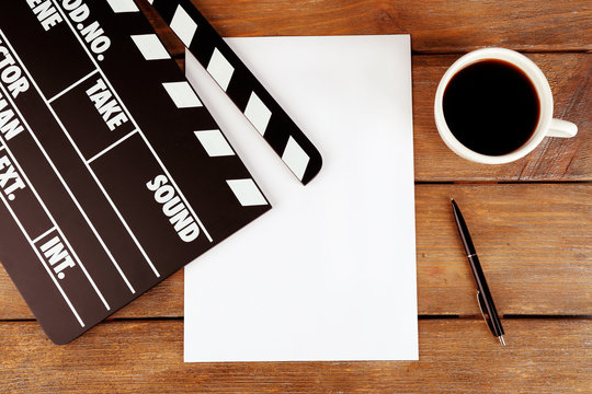 Movie clapper with paper, pen and cup of coffee