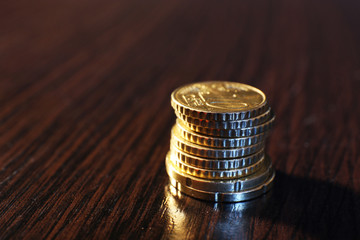 Stack of golden coins on wooden table background
