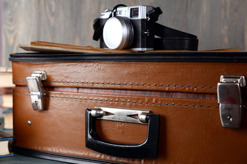 Vintage suitcase with camera on wooden background