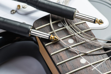 Frets of black electric guitar with cable