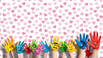 angemalte Kinderhände vor Wand mit Herzchentapete