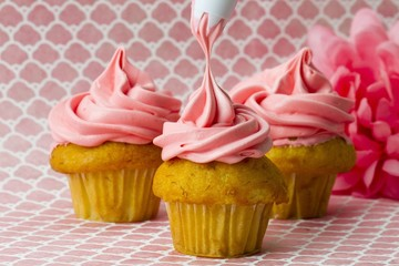 icing being applied to three cupcakes on pink