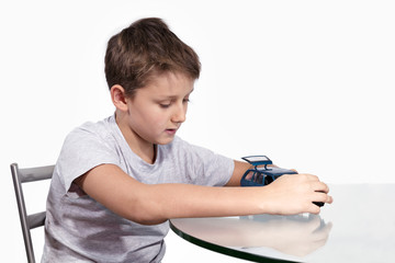 Boy playing with blue car on a glass table