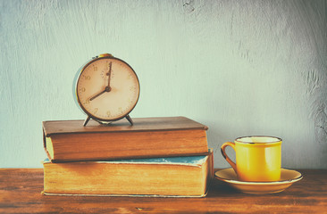 Image of old clock and coffee cup over wooden table. image is fi