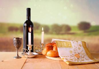 shabbat image. challah bread, shabbat wine and candelas on woode