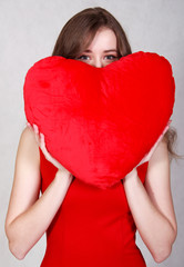 Portrait of a young attractive woman with a heart-shaped pillow