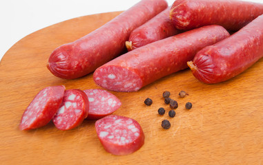 Smoked sausages on wooden desk isolated on white background