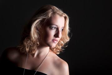 Junge hübsche blonde Frau im Licht und Schatten