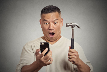 Shocked man looking at smart phone holding hammer