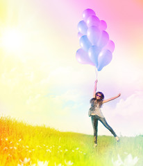 Happy girl flying with balloons on sunny summer meadow.