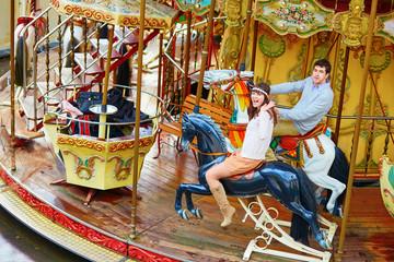 Happy couple on the merry-go-round in Paris