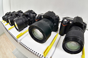 Reflex digital cameras with notepad in photoschool close-up