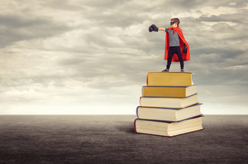 Education. Super hero boy standing on a pile of books