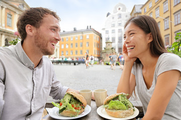 Cafe couple eating food sandwiches in Stockholm