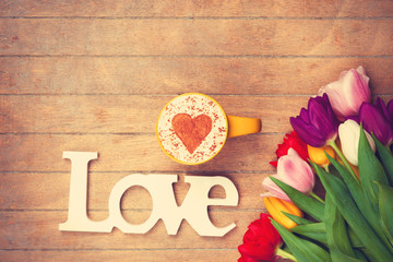 Cappuccino and word Love near flowers