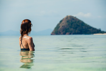 Woman sitting in water looking at island