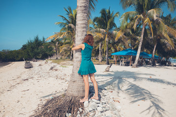 Young woman hugging a palm tree