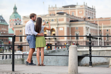 Couple taking smartphone photos in Stockholm city