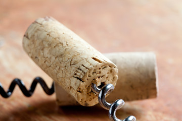 Two corkscrew with wine corks. Macro view. Closeup. Soft focus. Retro style. Paper texture background.