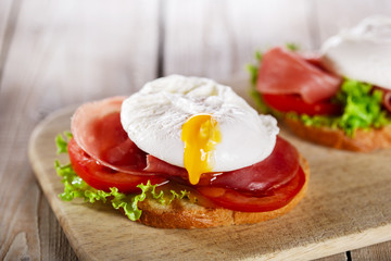 sandwich with prosciutto and poached egg tomato
