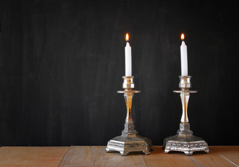 two candlesticks with burning candels over wooden table and blac