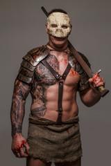 Muscular gladiator in skull mask