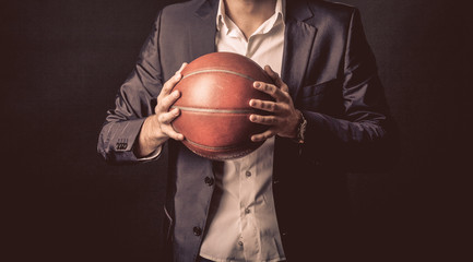 mature businessman holding basketball ball