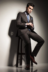 business man looking away while sitting on a stool