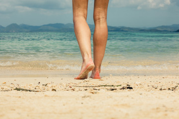 Feet and legs of young woman walking on beach